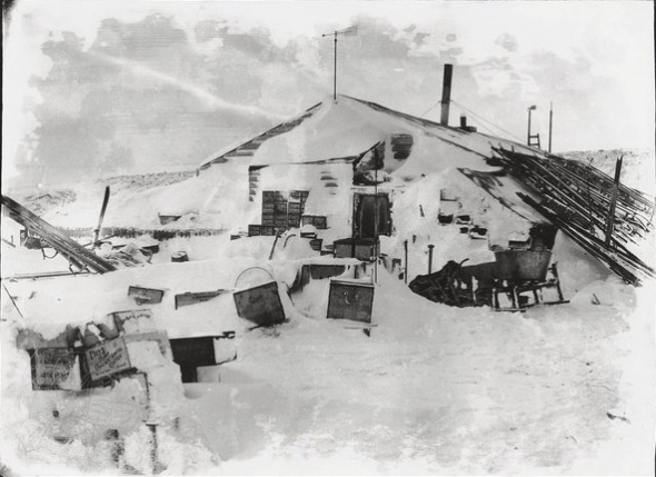 The hut at Cape Evans, showing the large number of stores stacked outside, including dozens of sledges leaning, boxes of Fry's cocoa and a bath tub.