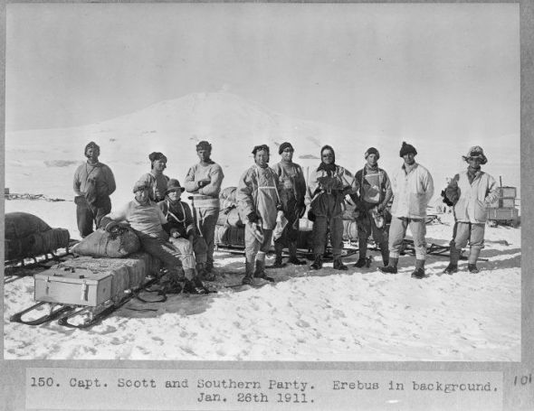 """Captain Scott and the Southern [depot-laying] Party .... Erebus in background. Photograph taken on the 26th of January 1911, by Herbert George Ponting."" Standing, left to right, are Crean, Keohane, Gran, Scott, Forde, Meares, Cherry-Garrard, Oates, and Atkinson, and sitting on the sledge, Wilson and Bowers."