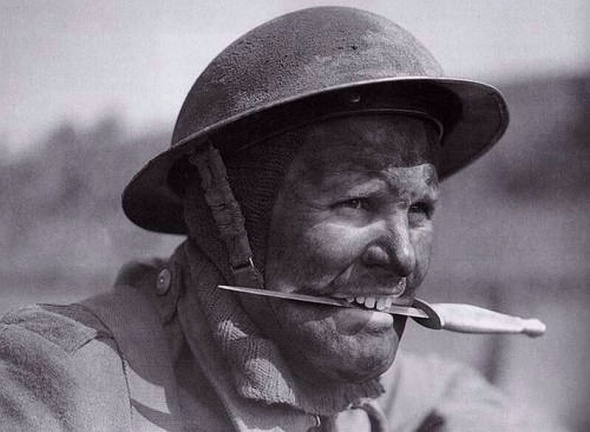 British soldier holding his fighting knife between his teeth. 1942