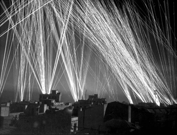 Those are the light trails that result from long-exposure photography of gunfire. Ack-ack is shorthand for anti-aircraft.