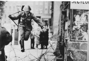 A soldier of the GDR jumping across the fence shortly before it was too late.